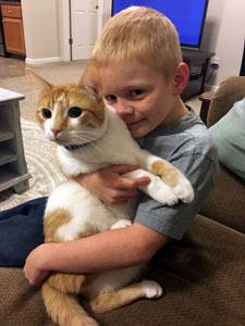 Boy closely hugging and holding Oliver