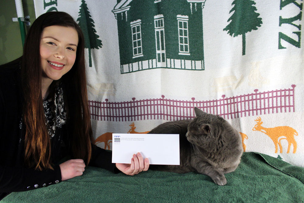 Chloe holding an envelope with Mona Lisa sitting nearby