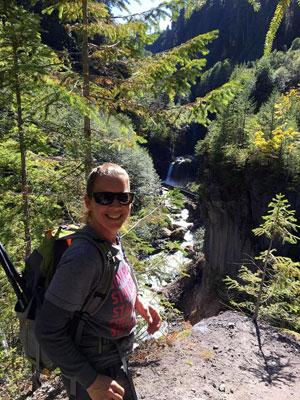 Dena Hugh on a hiking trail, smiling