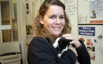 Dena Hugh holding a bi-color cat in her arms
