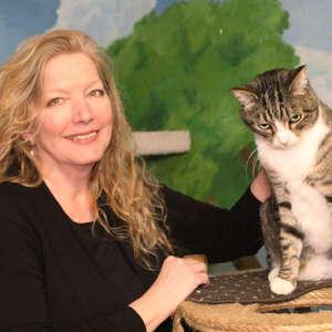 Secretary Margie McGhee petting a cat