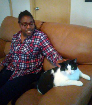 Nyla petting Jojo, who's sitting on the couch