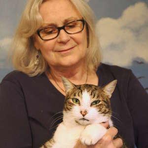Grants, property management Sandi Long holding a cat