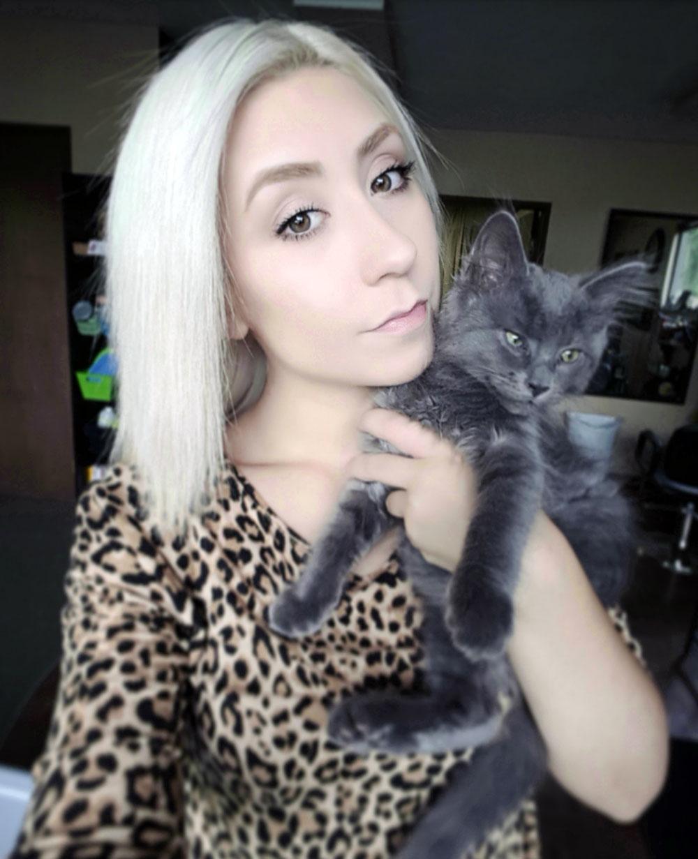 Tess holding kitten Gimm up near her face